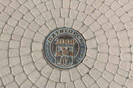 city coat of arms: Pyatigorsk, Russia - October 4, 2015:  Bronze medal on a street from cobblestones with coat of arms of the Pyatigorsk City Editorial