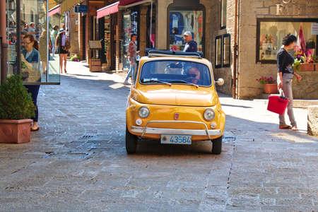 San Marino, Italie - le 22 Août, 2015: Vieille voiture jaune Fiat 500 dans la rue avec des gens à Saint-Marin
