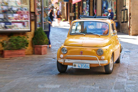 San Marino, Italy - August 22, 2015: Old small car Fiat 500 moves down the street of San Marino