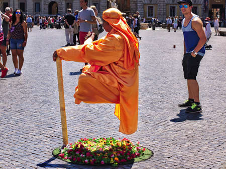 Roma, Italia - 18 de agosto de 2015: el hombre de la prenda naranja está flotando en el aire