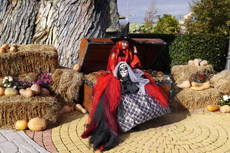 Adler, Russia - November 3, 2016: A pretty witch with head in her hands sitting on an old chest with gold. Celebration of Halloween in Sochi Park in Adler