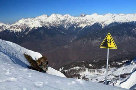 A sign warning of the danger of falling from the cliff. Ski resort Rosa Khutor, Russia