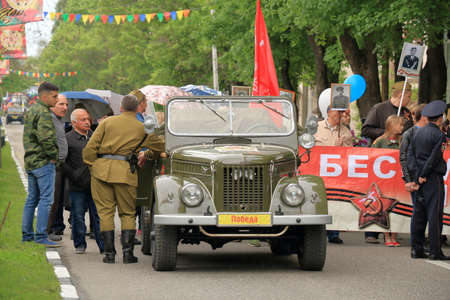 pyatigorsk: Pyatigorsk, Russia - May 9, 2017: Rare UAZ car in front of a column of people. Preparations before the commemoration of the Victory Day in World War II