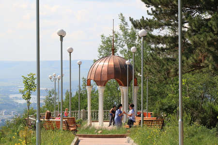 Kislovodsk, Stavropolsky Region, Russia - July 16, 2017: Tourists near an elegant gazebo with white columns and a copper dome in the Kislovodskiy National Park