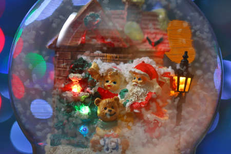 Santa Claus with a child and Teddy Bear near the house with street illumination close-up. Long exposure time
