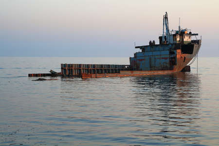 Evening. View of the old unknown abandoned barge in a bay on the Black Sea. Kabardinka, Krasnodar region, Russia 版權商用圖片 - 93849037