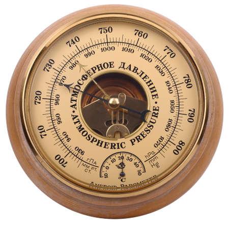 木製ボディの古い黄色茶色のアネロイド気圧計は、白い背景に隔離されています