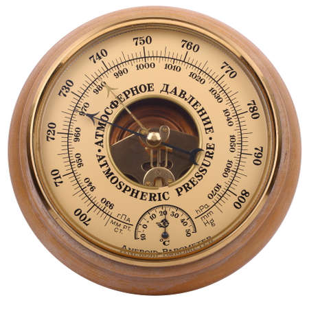 Old yellow-brown aneroid barometer in wooden body is isolated on a white background