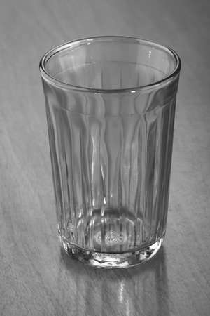 An empty faceted drinking glass on an old scratched desk. The concept of poverty or alcohol addiction Stock Photo