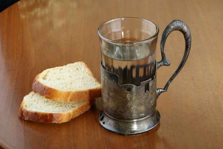 A faceted glass of hot water for tea in an ancient silver cup holder and two slices of bread on an old brown scratched table