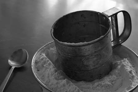 Old stainless steel cup flour sifter lies in a white enamel bowl on an old scratched table. Monochrome image