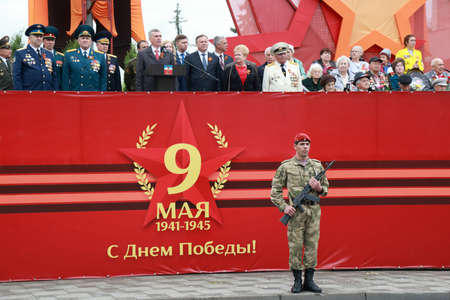 Pyatigorsk, Russia - May 9, 2018: A soldier with a red beret and AK-74M Kalashnikov rifle in the hands near the tribune with veterans. Victory Day parade in Pyatigorsk Editorial