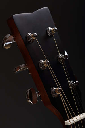 Six-stringed wooden acoustic guitar head with metal tuning pegs