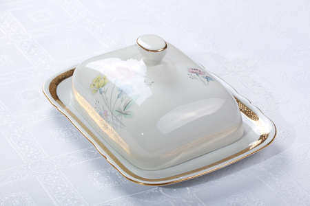 White porcelain butter dish with painted flowers on a white tablecloth