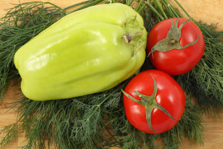 Bell pepper, two ripe tomatoes and bunch of the fresh dill leaves on a wooden cutting board Stock Photo