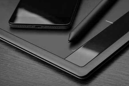Smartphone and graphic tablet with a special pen-like stylus on a wooden table. Details of workplace of an digital graphics art designer. Monochrome image