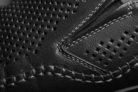 Natural black leather with perforation in form of the rhombus. Stitched parts of the shoes. Abstract background