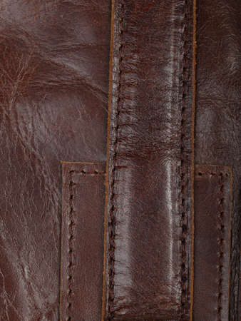Stitched brown leather parts. Details of a mans bag. Abstract background