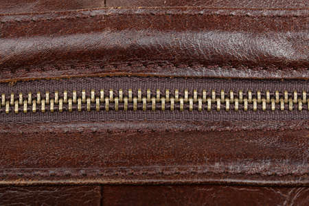 Zip fastener on a brown leather surface close-up. Details of a mans bag