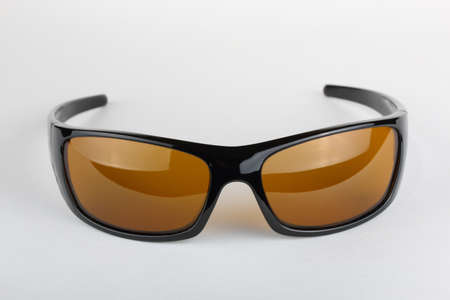 Single sunglasses with black plastic frame and yellow glass on a white background Reklamní fotografie