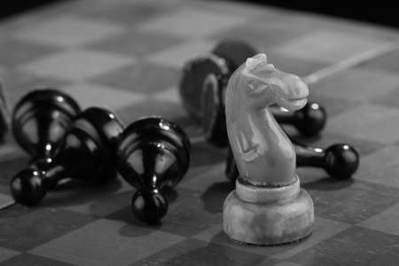 White chess knight swept through the army of enemy pawns on an old scratched chessboard. Rush attack. Black Army is defeated. Concept of conflict and active actions. Black and white image