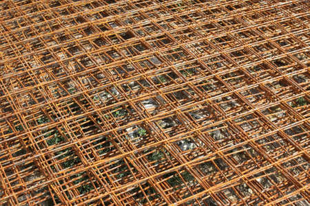 Stacked rusty steel wire mesh for slab concrete work at the construction site. Background Stock Photo