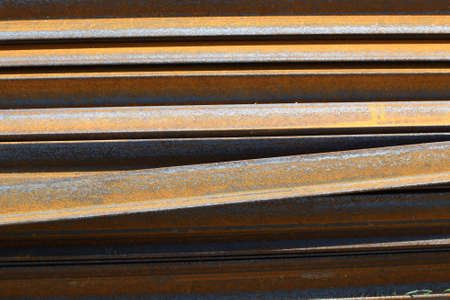 Rusty metal L-bar angle at the warehouse of metal products piled in the open air. Background