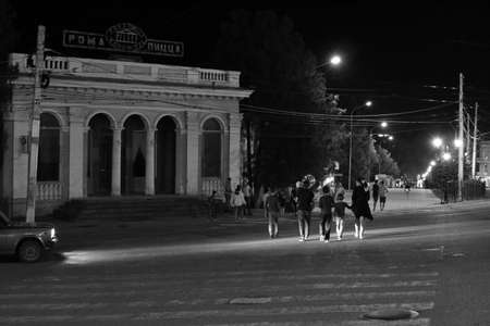 Pyatigorsk, Russia - August 13, 2018: Unknown people cross the crosswalk at night. Noisy image