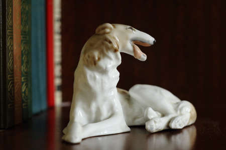 Old porcelain figurine of a dog of breed Russian Greyhound on a bookshelf Stock Photo