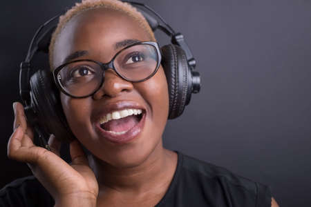 portrait of african girl listening to music on headphones, smiling. On a dark background Archivio Fotografico - 138003008