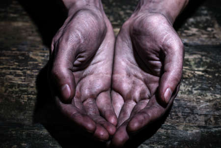Male dirty worker hands asking for palms on dirty wooden background. The concept of assistance, begging, poverty. Share hope. Beg for money.