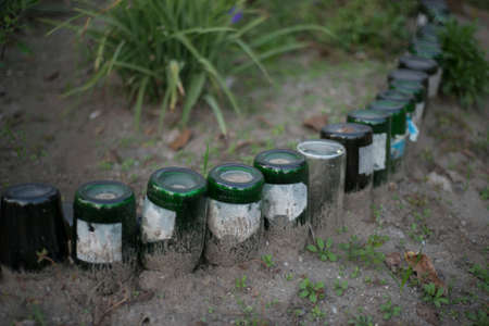 glass bottles in the form of a decorative fence. Glass contamination. Glass waste in nature. Recycled glass