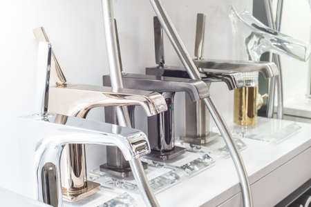 a variety of faucets taps on a white shelf in the store counter 스톡 콘텐츠