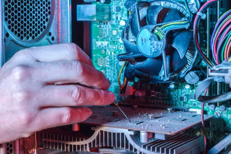 Close-up of professional equipment master repairing computer software. The hand of a master with a screwdriver repairs microcircuit technology. Cleaning computers from dust. Repair equipment. Customer Service Issue