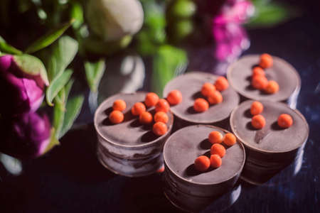 bouquet of beautiful flowers and chocolate on wooden surface