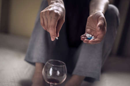 a young girl sitting in a dirty room, with a glass of wine, and holds pills in her hand. Poisoning when mixing alcohol and drugs. Polydrug addiction in women. Death due to an overdose of potent, sedative drugs with alcohol