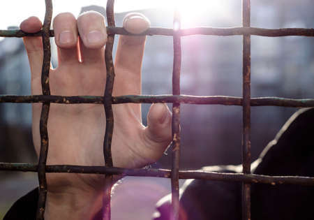 Hands of the prisoner on a steel lattice close up the prisoner, behind bars, holds his hands by the bars, sticking them out of the prison bars Stock Photo