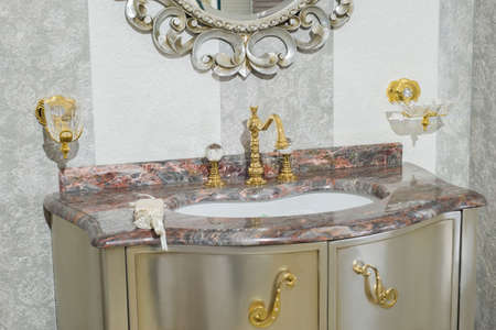 Interior in the bathroom, vintage mirror and expensive marble washbasin, stainless steel tub, with gold handles close-up. Stockfoto