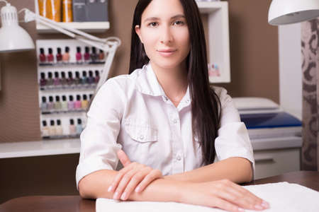 portrait of a beautiful girl - a cosmetics seller in a beauty salon, sitting at a table, against a background of cosmetics. A girl with flawless hair sells skin and hair care products.