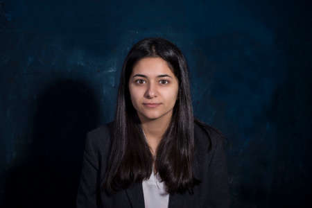 portrait of a beautiful indian young girl looking at the camera, smiling. On a dark blue background. Business lady, Indian appearance, Assyrian nationality. Young woman in a suit