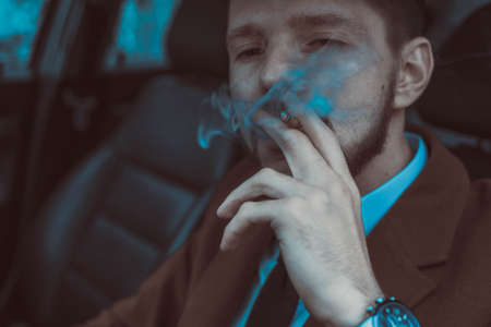 Portrait of a young guy, thirty years old, close up, driving a car smokes a cigarette. Businessman with a beard in a business suit, brutally smokes a cigarette. In creative processing. A bearded man smoking a black cigarette, releasing thick smoke.