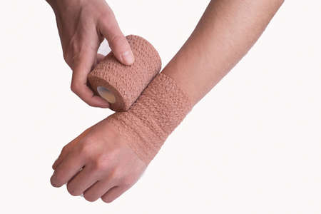 Coban Self-Adherent Bandage is a comfortable, lightweight bandage for sustained, reliable compression. close-up of a mans hand. self-locking wrist joint in case of injury, with the help of an elastic American cobane bandage. Sports medicine, injuries and diseases of the wrist joint, tunnel syndrome. Fixation and immobilization of the injured area of the arm