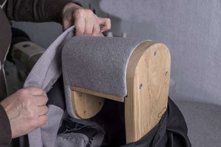 the process of forming the shoulders of the jacket. The hands of the clothing master, using the forming stand to form the shoulders of the jacket, smooths the shoulders of the fabric jacket. Stages of making clothes, tailoring a suit. Ironing clothes made of high quality fabric. Shoulder Shaping