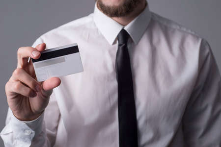 Portrait of a bearded business man in a white shirt and tie holding a credit card in his hand. On a gray background. credit history concept by paying by credit card for online purchases. The use of plastic bank cards worldwide. Refusal to use cash in favor of credit cards
