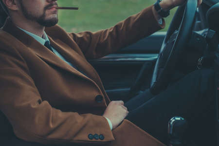 Portrait of a young guy, thirty years old, close up, driving a car smokes a cigarette. Businessman with a beard in a business suit, brutally smokes a cigarette. In creative processing. A bearded man smoking a black cigarette, releasing thick smoke. Stock fotó