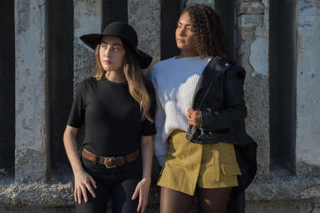 a girl in a leather jacket and a white sweater, a girlfriend in black jeans and a black hat, young Mexican girls at the textured wall, sister's day. Fashion shooting Banco de Imagens - 138263845