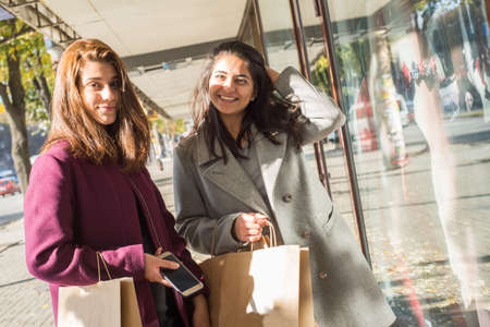 two beautiful young girlfriends, of Indian appearance. Girls stand at the window with things, smiling, pointing a finger at the goods. Buying new things, joys. Young beautiful indian girls shopping Archivio Fotografico