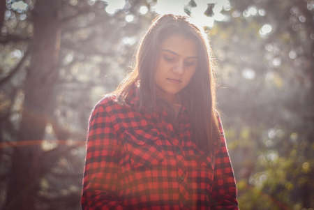 Portrait of a beautiful young smiling happy girl walking in the autumn forest. Romantic walk, the mystery of the girls. Autumn sale background. Plaid shirt. Reklamní fotografie