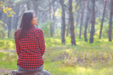 portrait of a beautiful young girl, from the back. Sits in the autumn forest in a checkered shirt. The mystery of the girls. Loneliness. Autumn depression. Suicidal mood