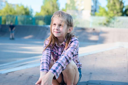 little teenage girl, schoolgirl sitting on a skateboard, in a sports park, in a plaid shirt, happy, smiling